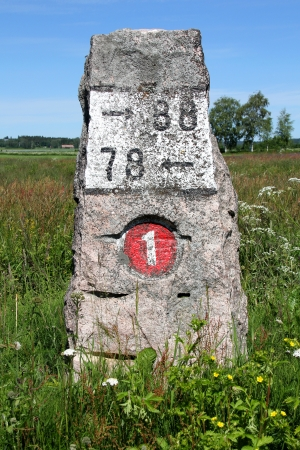 Old milestone made of granite by highway 110, previously number 1, in Kitula, Finland with summer landscape