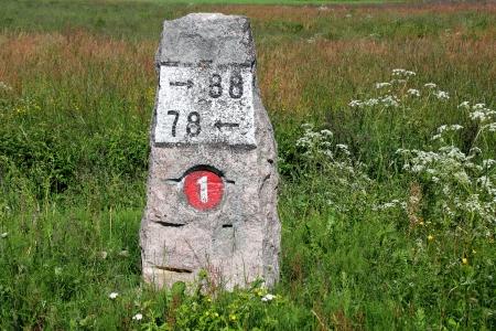 Antiguo hito de granito por la autopista 110 (anteriormente el número 1) en Finlandia en verano.