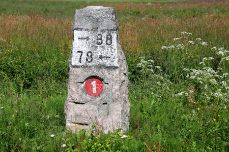 kilometre: Old milestone made of granite by highway 110 (previously number 1) in Finland at summer.  Stock Photo