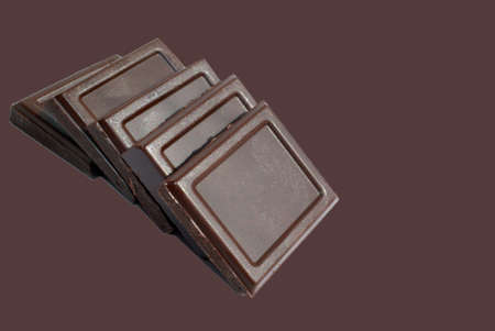 Pieces of dark chocolate on brown background. photo
