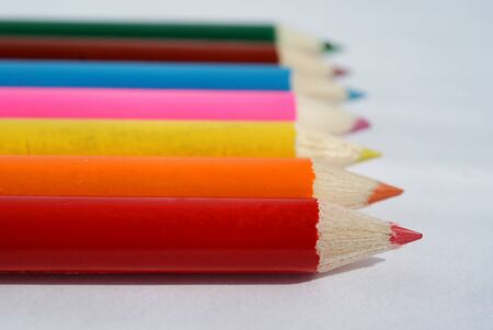 Row of color pencil crayons over white. photo