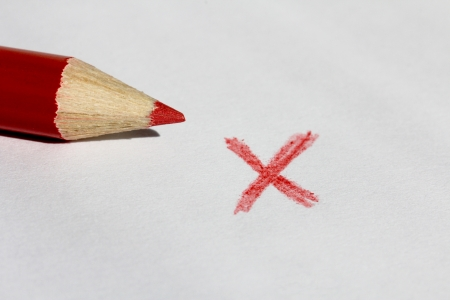 Red color pencil and x mark on natural, white paper for incorrect or wrong
