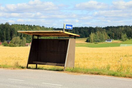 Rural bus stop shelter with wheat field and village background   photo