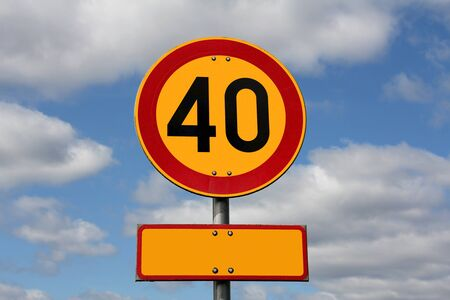 Maximum Speed 40 km per hour with blank letter plate for your text, with blue sky and clouds as background   photo