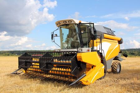 heavy equipment: Yellow modern combine harvester on stubble field at end of summer