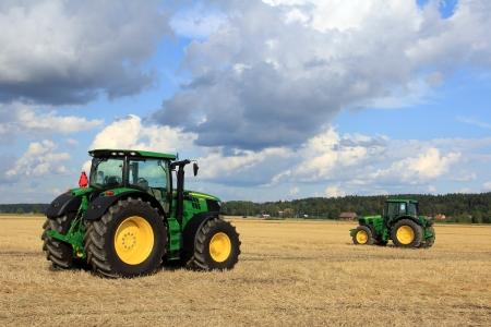 Salo, Finlandia - 18 de agosto 2012 Two tractores John Deere, modelo 6210R y 6930 en la exhibición en el campo Puonti en Salo, Finlandia 18 de agosto 2012 Editorial