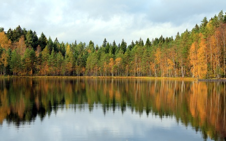 Quiet rural lake in Finland with colorful fall reflections. photo