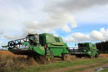 SALO, FINLAND - OCTOBER 8, 2012 - Two combine harvesters by wet field on October 8, 2012. Heavy rainfall and flooding in area has caused cereal and oleiferous plant crops to be lost.  Stock Photo - 15699829
