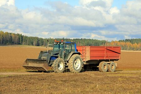 Blue tractor and agricultural trailer on flax or linum field in harvest time in Finland  photo