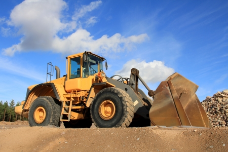 Yellow wheel loader at sand pit against blue sky