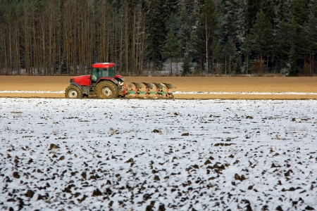 Red tractor and plough on field in early winter