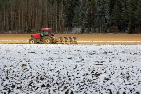 Red tractor y el arado en campo en el comienzo del invierno Foto de archivo