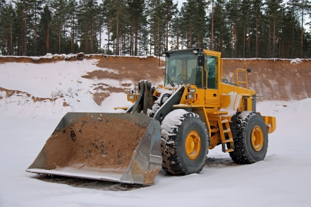 Yellow wheel loader at sand pit in winter snow  photo