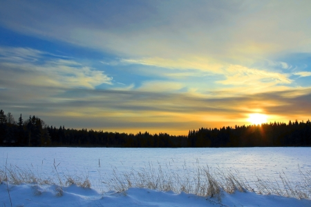Last rays of the sun over snow covered fields on a cold December evening in Finland