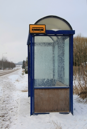Local bus stop shelter in winter snowfall with hoarfrost on panels. photo