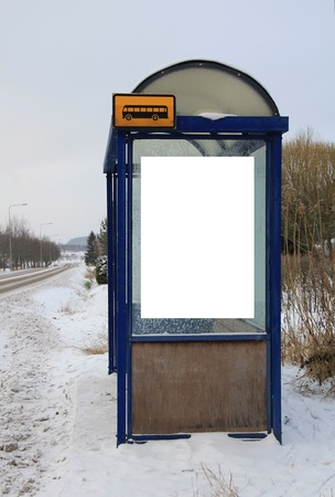 Local bus stop shelter in winter with one blank billboard for your advertisement.  photo