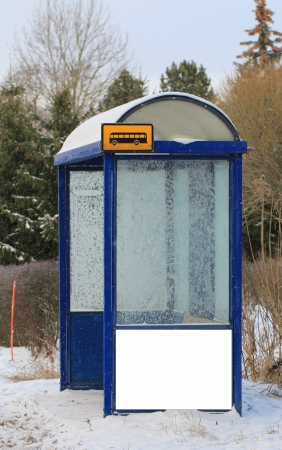 Urban bus stop shelter in winter with one blank billboard for your advertisement.  photo