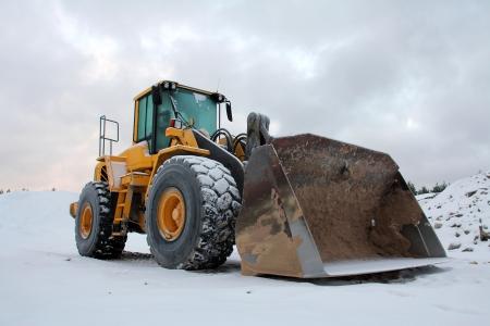 Cargadora de ruedas amarillo en foso de arena en la nieve del invierno.