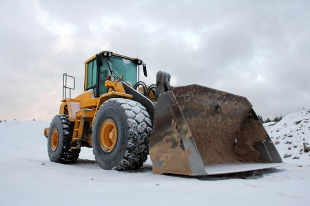 Yellow wheel loader at sand pit in winter snow.