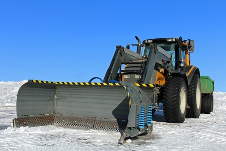 Snow plow mounted on a yellow tractor with snow and blue sky as background. photo