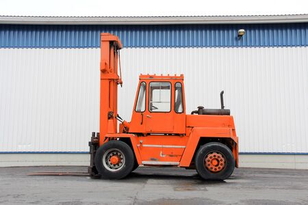 Orange forklift truck by an industrial building. photo