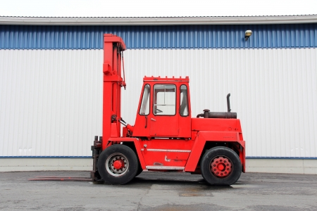 Red forklift truck by an industrial building. photo