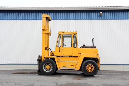 Yellow forklift truck by an industrial building. Stock Photo - 19140453