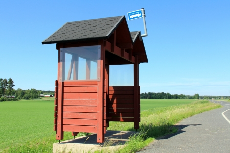 Rural bus stop shelter made of wood and painted red by highway on a sunny day at summer. Space for your advertisement. photo