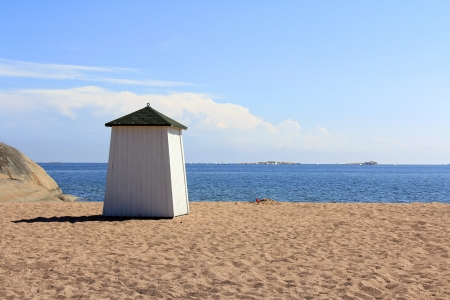Wooden beach hut facing the blue sea and ships on the horizon in Hanko, Finland. photo