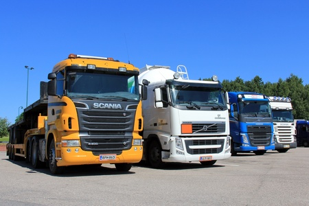SALO, FINLAND - JUNE 21, 2013: Row of trucks on a parking lot in Salo, Finland on June 21, 2013. The Finnish government will allow heavy goods vehicles of up to 76 tonnes on roads beginning August 1, 2013. Stock Photo - 20473910