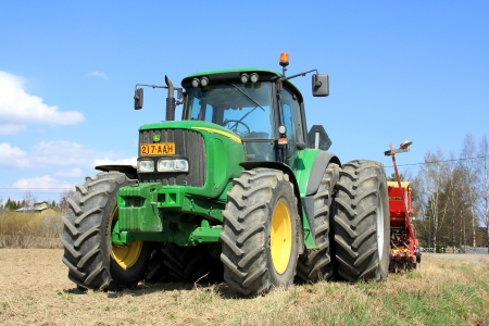 SALO, FINLAND – MAY 11, 2013: John Deere 6620 agricultural tractor and cultivator on field in Salo, Finland on May 11. On June 28, John Deere announces New Mobile Version to parts and services for a convenient access even in field. Stock Photo - 20578068