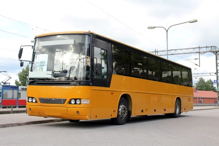 Yellow bus at the railway station waiting for passengers. Редакционное