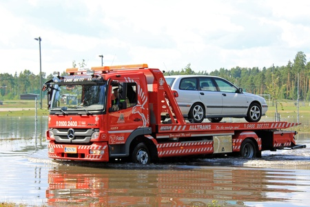 Karjaa, Finlandia - 27 de julio de 2013: Mercedes grúa rescatar un coche de la zona inundada en Karjaa, Finlandia el 27 de julio de 2013. Las fuertes lluvias y truenos el 26 de julio causaron inundaciones en el centro de Karjaa.