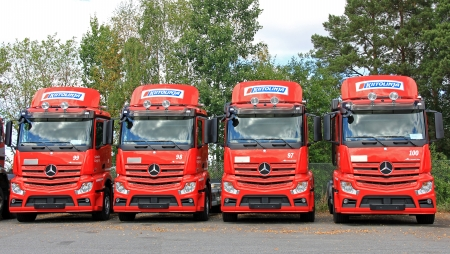 LIETO, FINLAND - AUGUST 3  Row of red Mercedes Benz Actros trucks in Lieto, Finland on August 3, 2013  The Actros truck has Predictive Powertrain Control  PPC , which recognises the topography ahead and helps to keep the fuel consumption low