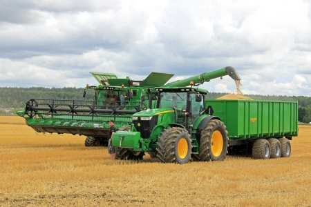 SALO, FINLAND - AUGUST 10  John Deere Combine harvester unloading grain on Palmse 1900 trailer behind Deere 7280R tractor, at the annual Puontin Peltopaivat Agricultural Show in Salo, Finland on August 10, 2013
