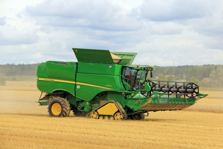 deere: SALO, FINLAND - AUGUST 10  John Deere Combine s670i harvesting barley at the annual Puontin Peltopaivat Agricultural Show in Salo, Finland on August 10, 2013