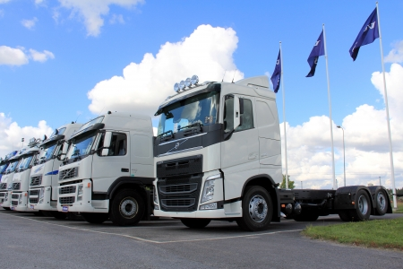 LIETO, FINLAND - AUGUST 31: Row of white Volvo FH trucks on August 31, 2013 in Lieto, Finland. Volvo Trucks new range goes on public display for the first time at the Comtrans Exhibition in Moscow 10–14 September. Editorial