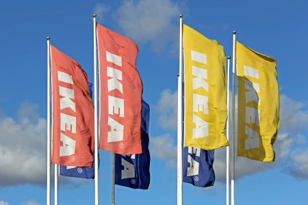 RAISIO, FINLAND – SEPTEMBER 21: IKEA flags against sky at IKEA Raisio Store on September 21, 2013 in Raisio, Finland. As of January 2008, the company is the worlds largest furniture retailer. Stock Photo - 22358773