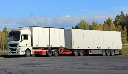 New and big white semi trailer truck on a parking lot in autumn.