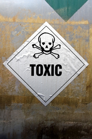 Grungy Toxic sticker label attached on rusty metal surface  photo
