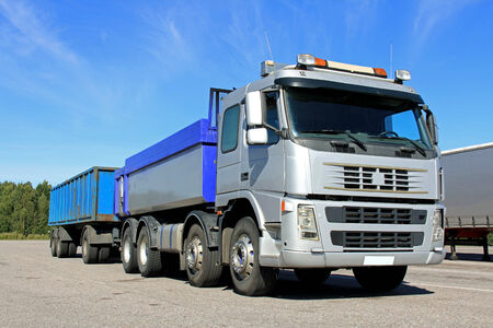 tipping: Grey gravel or dumper truck with trailer on a sunny day.