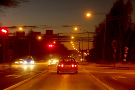 Coches detuvieron en un semáforo en rojo en una carretera iluminada en tiempo de la oscuridad, visión borrosa.