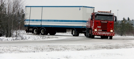 LIETO, FINLAND - DECEMBER 8, 2013: Scania tow truck towing a trailer on December 8, 2013 in Lieto, Finland. Finland does not require winter tyres on heavy goods vehicles, but in 2013 neighboring Sweden introduced a requirement for winter tyres on both tru