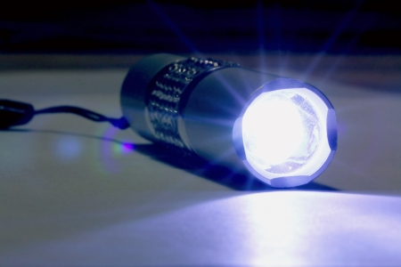 torchlight: Close up of a glowing flashlight in the dark