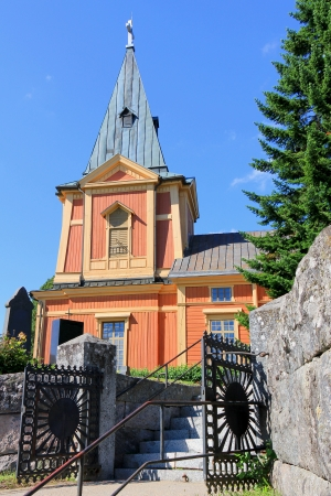 west end: Entrance to the wooden Punkalaidun church, Finland. The church was designed by Johan Bjorman, built in the 1770s and it has a massive bell tower at the west end of the church building.