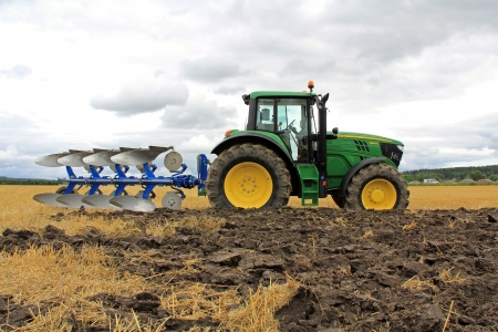 deere: SALO, FINLAND - AUGUST 10, 2013: John Deere 6150M agricultural tractor and plow at the annual Puontin Peltopaivat Agricultural Harvesting and Ploughing Show.
