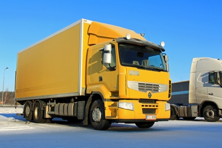reusing: FORSSA, FINLAND - JANUARY 18, 2014  Yellow Renault Premium 410 delivery truck on parking lot in arctic conditions  Renault Trucks aim to manufacture their vehicles reusing a maximum amount of its component materials, 92  of the parts being recyclable