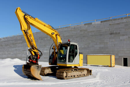 Yellow excavator on a construction site in winter  photo