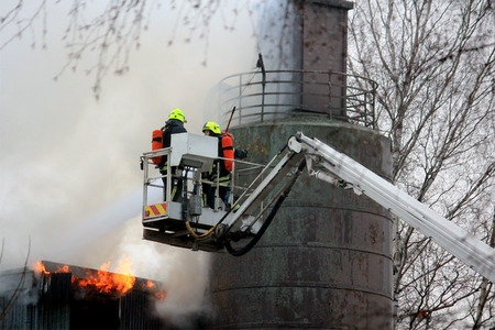 SALO, FINLAND - FEBRUARY 16, 2014  Firefighters extinguishing flames on a hydraulic crane platform at the Salo Cement Plant, which breaks out in fire twice on the same day