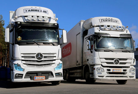 daimler: LIETO, FINLAND - MARCH 22, 2014: White Mercedes Benz Actros trucks on a yard. With the TopFit Truck project, Mercedes-Benz is making drivers the focus of its research.